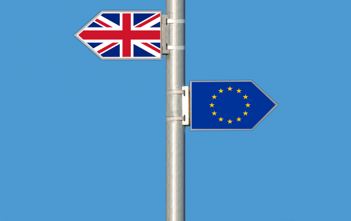 UK flag, EU flag pointing different directions for Brexit
